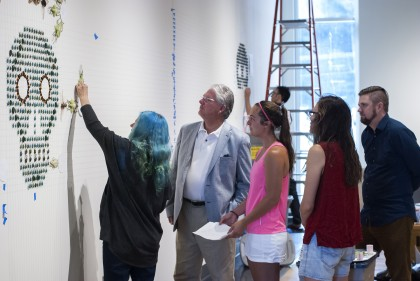 Installation artist Jennifer Angus works with students, and even President Jake Schrum, to instal...