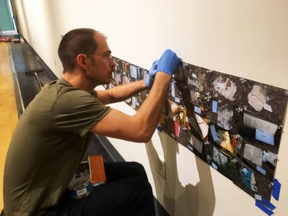 Artist Micah Bloom works to hang hundreds of photographs in his installation of Codex, a site spe...