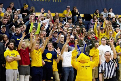 The Swarm, a student club geared towards supporting athletics, cheers along supporting athletics ...