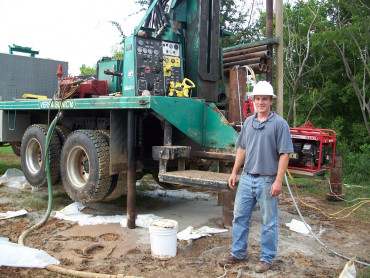 Alumnus Will McBryde installs a monitoring well in Alabama