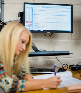 Student in front of computer screen showing graphs from data acquisition software