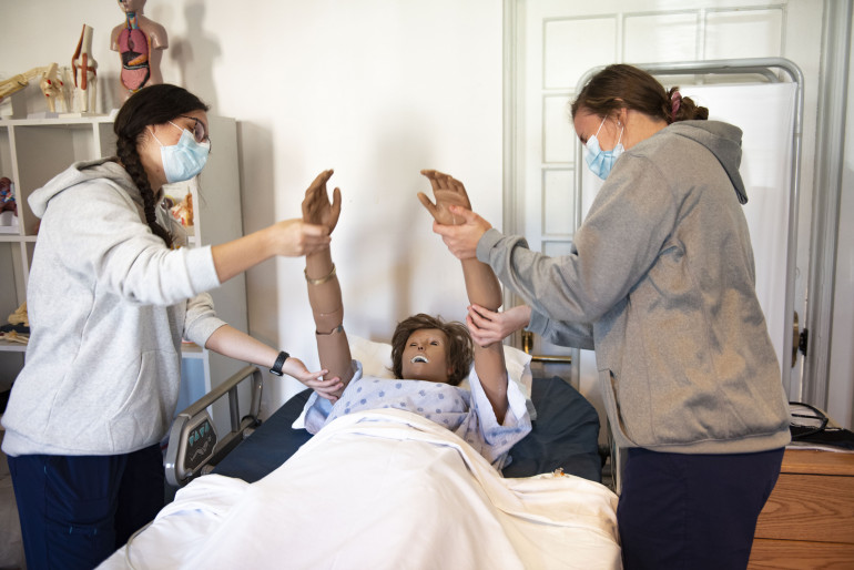 "CNA Students working with a ""patient"""