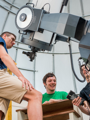 Students working the telescope controls in the observatory.