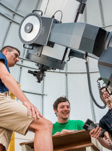 Students working the telescope controls.