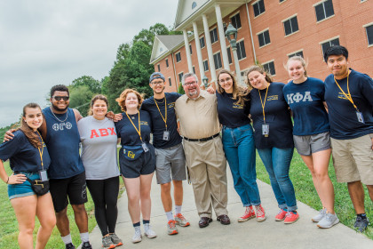 President John W. Wells poses with students during move-in day.