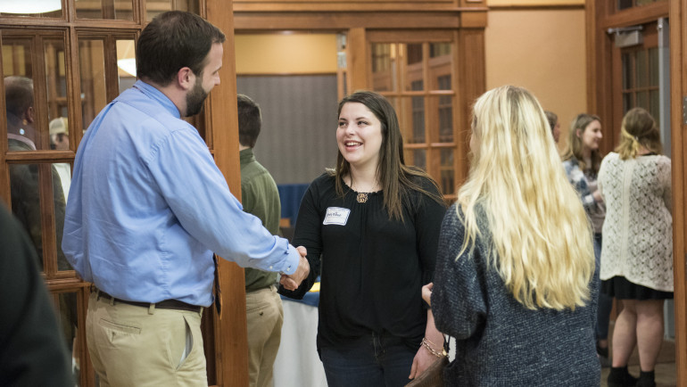 Students shaking hands and connecting with alumni.