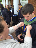 Alumni assist students with regalia before annual commencement exercises.