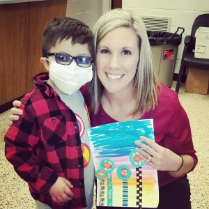"Emily Boyles with her son's best friend, ""Mighty Max,"" and a piece of artwork he did for her ..."