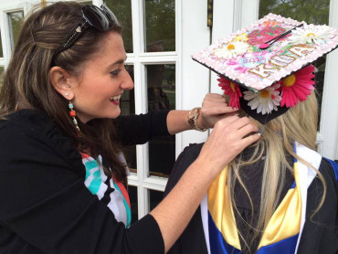 Volunteers help seniors get ready for commencement.