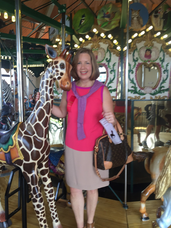 Karen Griffey Todd poses with Rothschild, the carousel giraffe she adopted.