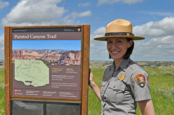 Laura Holley with one of her trailhead exhibit signs (1 of 25 installed spring of 2016).