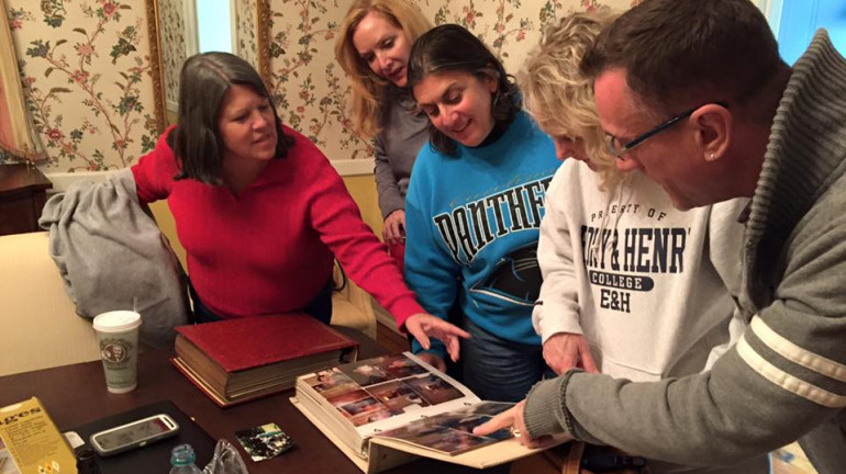 Friends from the 80s era gathered with old photo albums to recall friends and stories.