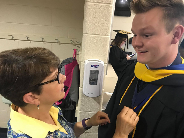 Suzy Copeland Burke (E&H '86) helps Brandon Minton (E&H '18) with his regalia b...