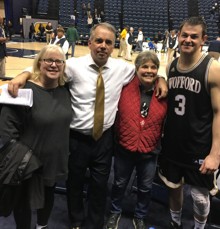 Head Wofford men's basketball coach Mike Young (in the tie) posing with friends and a Wofford player.