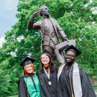 Graduates in front of the Patrick Henry statue.