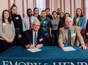 President Jake Schrum signs documents with Paul L. Phillips '64 surrounded by students from the B...