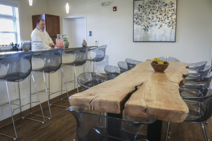 The kitchen of The Village Community Center features a dining table made from a tree that was loc...