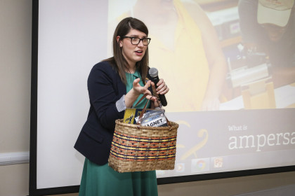 Rachael Wilbur shows the crowd the basket of prizes they can win if they share their favorite pag...