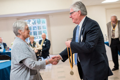 President Schrum presents medals to members of the class of 1968.