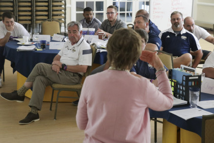 Head football coach Curt Newsome listens as Becky Sparger of the Southwest Virginia Mental Health...
