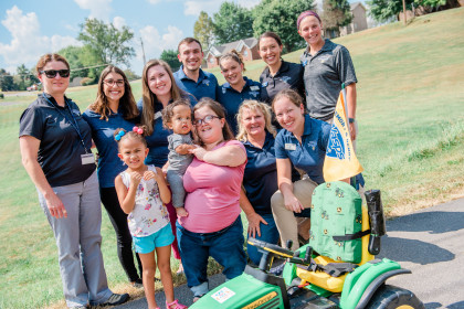 Students and faculty gather with Zavier and his mother with the modified tractor.