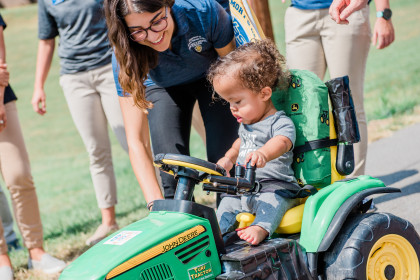 Zavier tries out his tractor with help from a student.