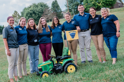Students and faculty stand with the modified tractor.