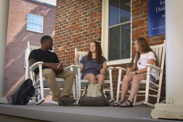 Students sit on the front porch of the Inclusion & Dialogue Center.