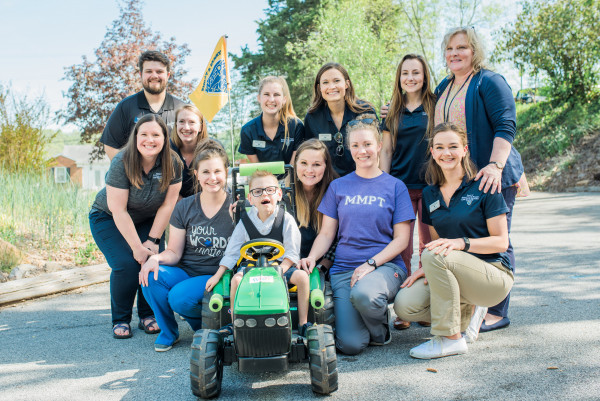 School of Health Science students present Creed Rosenbalm with his new tractor in part with Child...