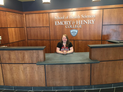 Here, Ms. Dowell, MEd, Program Manager of the MPAS Program, sits at the SHS lobby desk (this is j...
